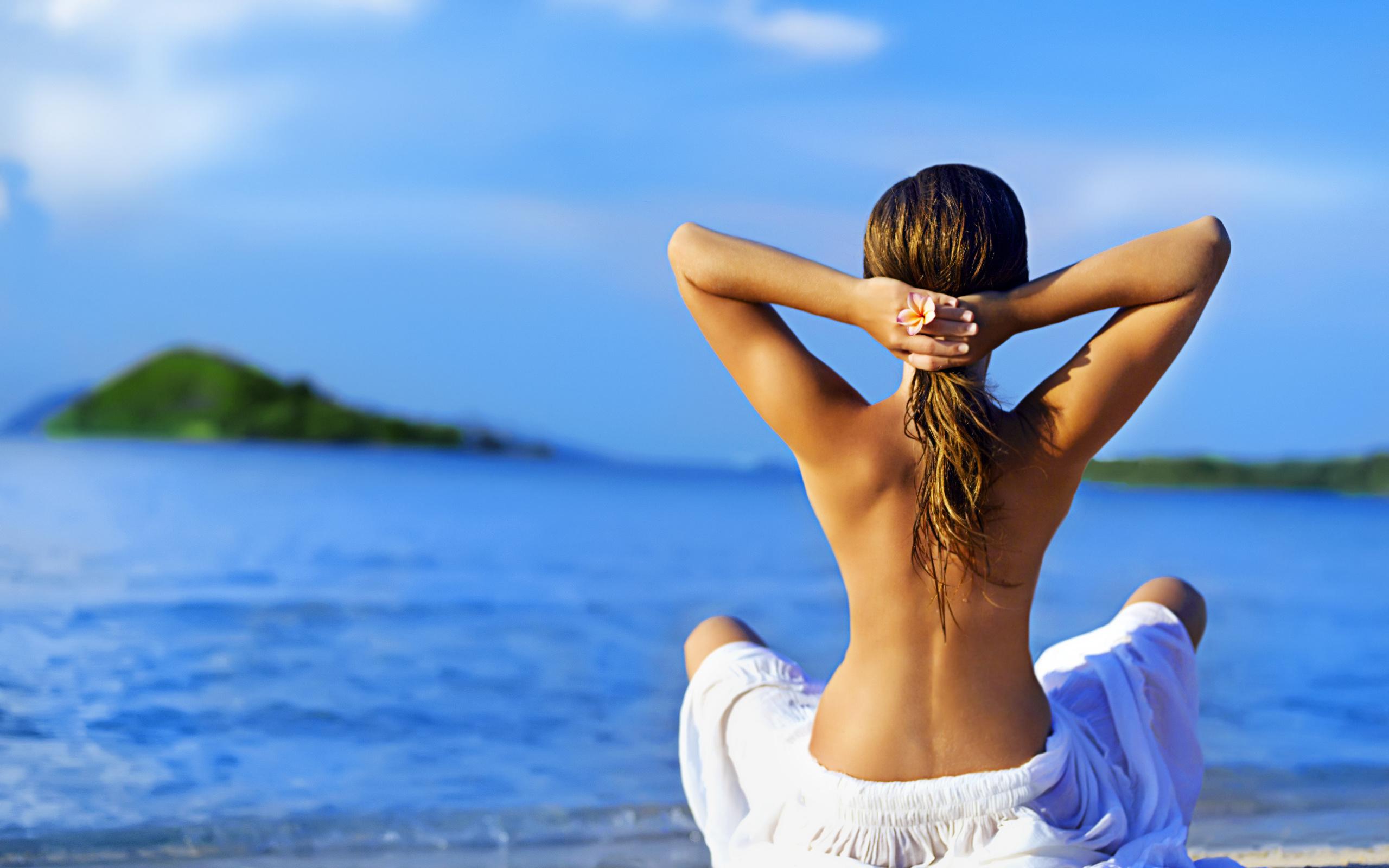 Девушка спиной на море с поднятыми руками