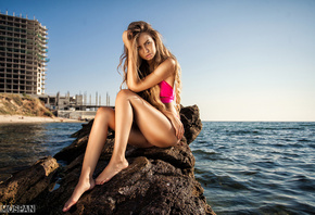 Liubov Guliak, women, model, brunette, sitting, ass, long hair, wavy hair, sea, water, stone, beach, hands on head, portrait, sky, building, swimwear, looking at viewer, blonde, Alexander Mospan