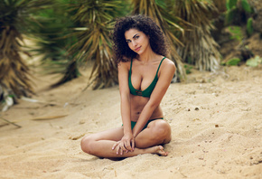 women, tanned, legs crossed, belly, sand, green bikini, smiling, depth of field, curly hair