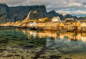 the sky, water, clouds, reflection, landscape, mountains, nature, rocks, shore, tops, the bottom, boats, Norway, houses, pond, the village, piles, The Lofoten Islands