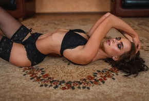 women, on the floor, closed eyes, garter belt, ribs, belly, pierced navel, lying on back, hands on head, arched back, black lingerie, tattoo, brunette