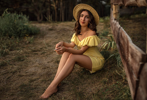 women, skinny, yellow dress, women outdoors, brunette, polka dots, hat, fence, necklace, smiling, trees, sitting