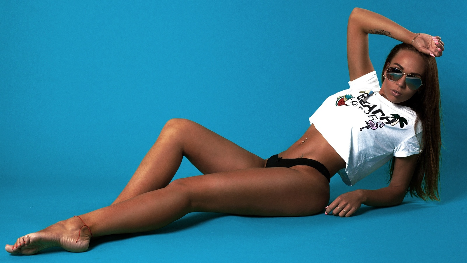 women, tanned, t-shirt, sunglasses, blue background, thong, tattoo, belly, pierced navel, pink nails