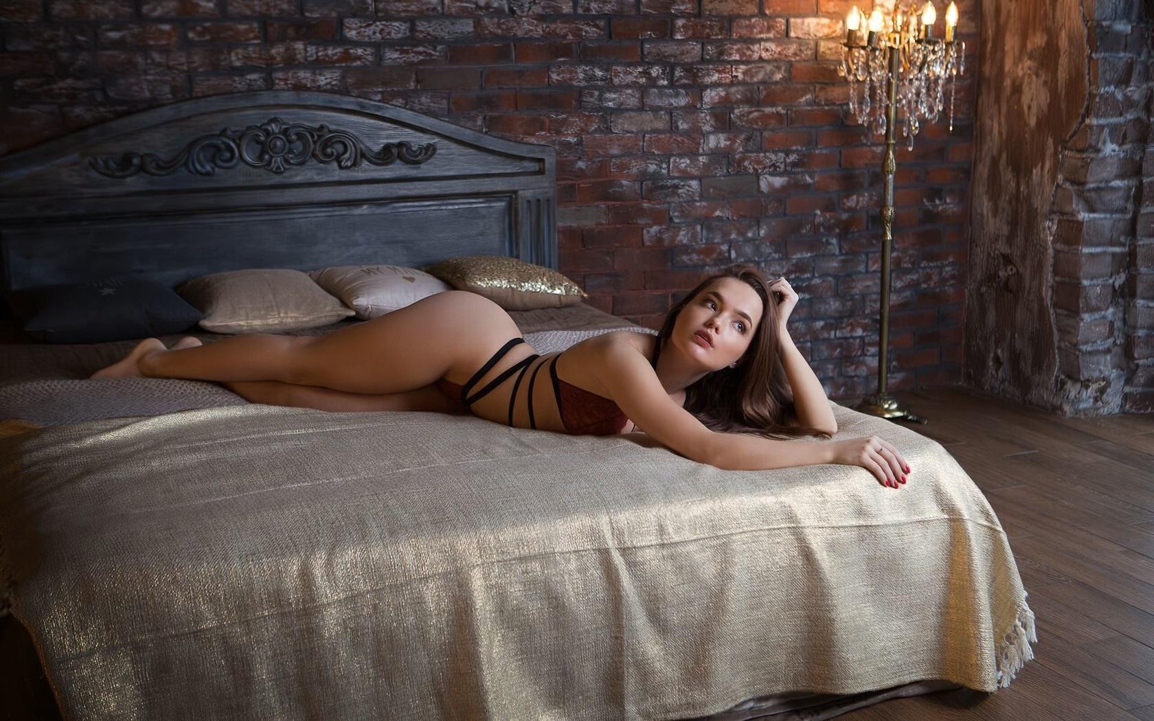 women, in bed, red lingerie, wall, bricks, red nails, looking away, lamp, комната,стена,кирпич,канделябр,кровать,покрывало,подушки,девушка,модель,позирует,волосы,шатенка,брови,глаза,взгляд,в сторону,губы,помада,, кольцо,стройная,фигурка,талия,бедра,лифчик