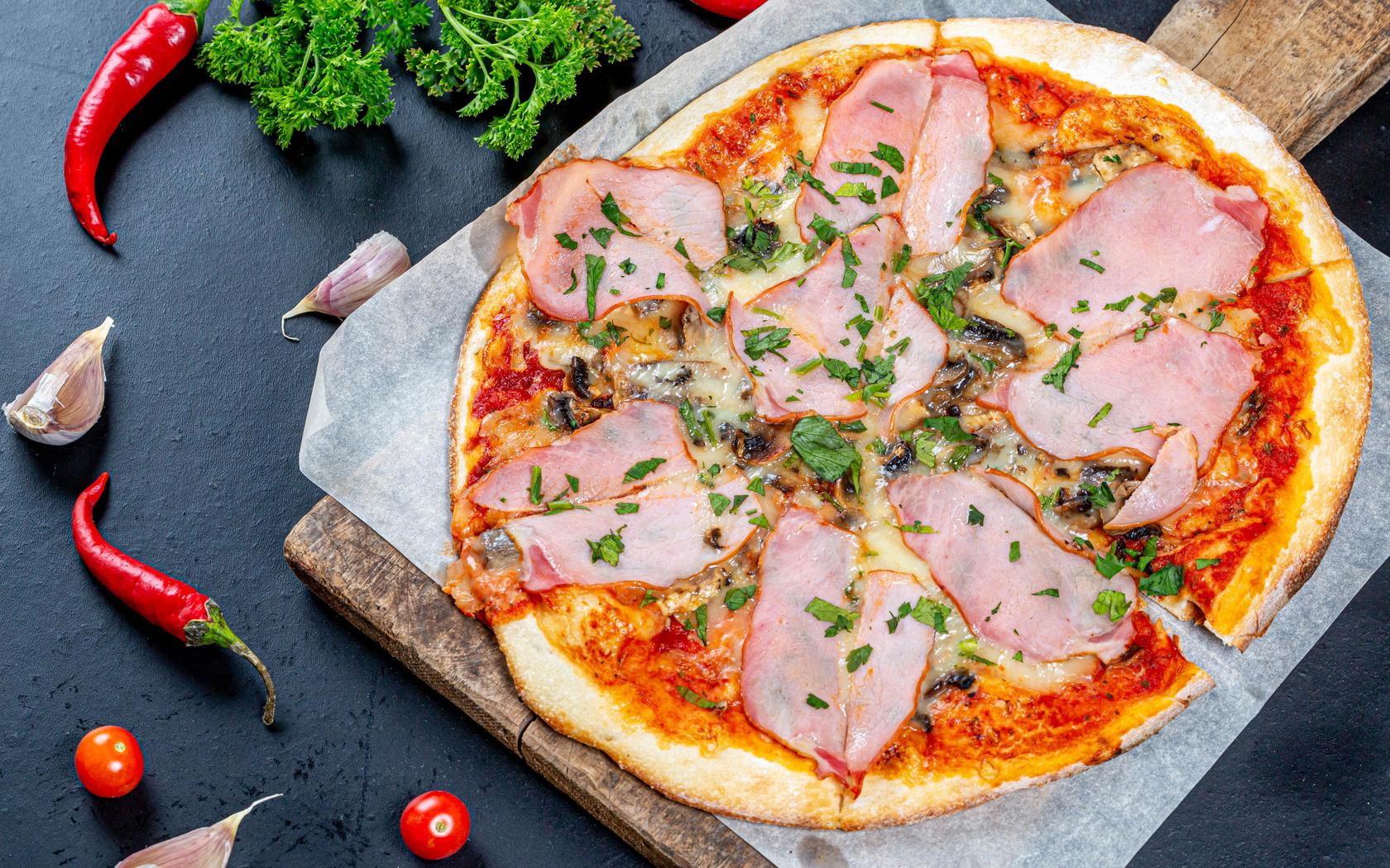 пицца, с ветчиной и грибами на столе с перцем, чили, чесноком и петрушкой