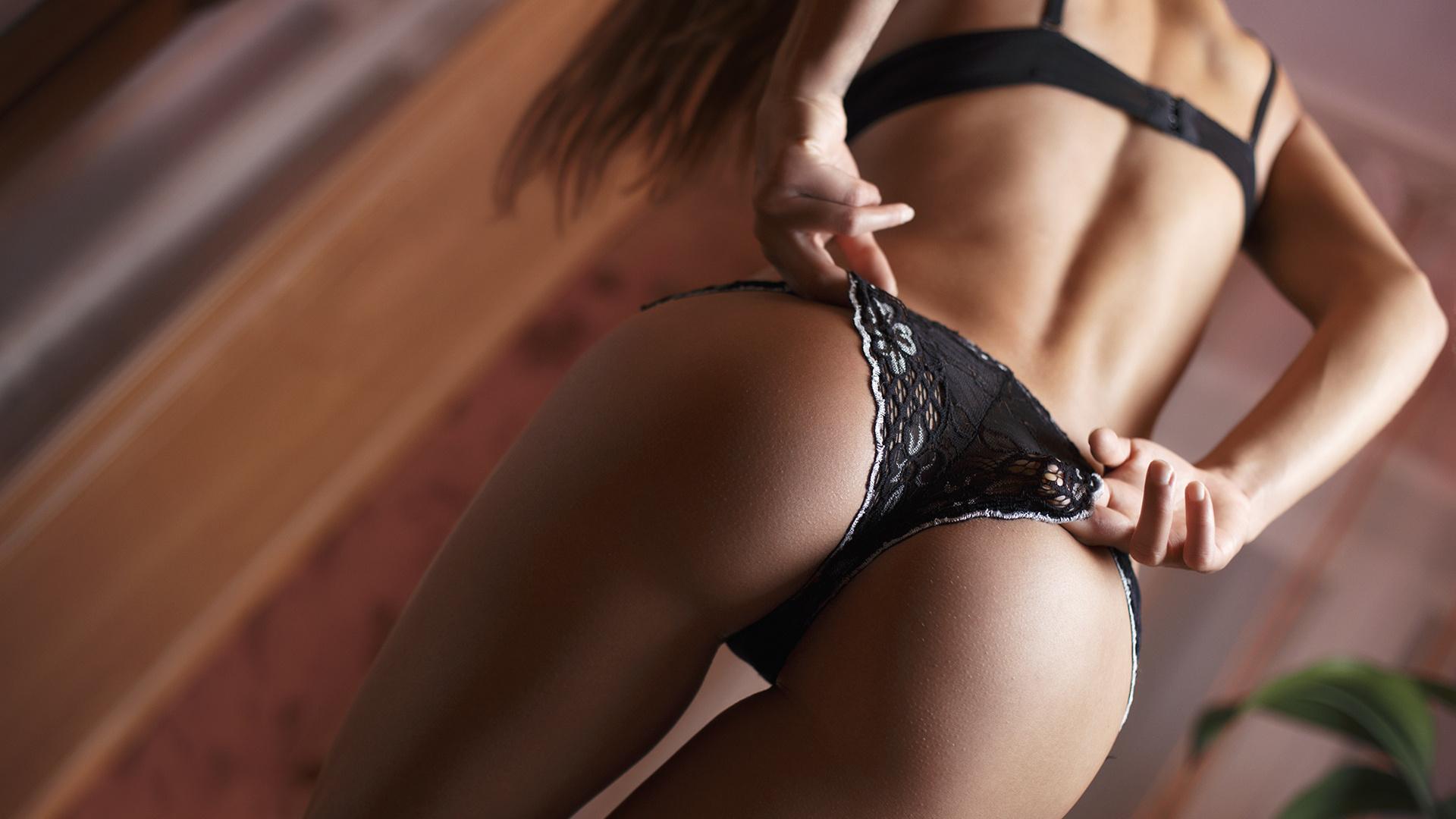 Красавица пытается сексуально снять с себя черные трусики